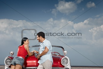man and beautiful woman leaning on cabriolet car