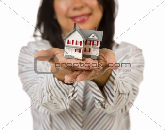 Attractive Multiethnic Woman Holding Out In Front of Her a Small House Isolated on a White Background.