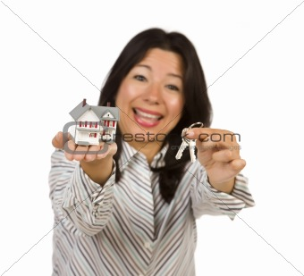 Attractive Multiethnic Woman Holding Small House and Keys Isolated on a White Background - Focus is on the house and keys.