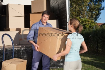 Couple carrying box into the truck