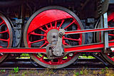 red wheels of an old steam locomotive standing on rail