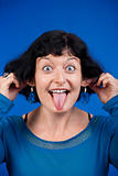 woman sticking out her tongue and pulling her ears - isolated on blue