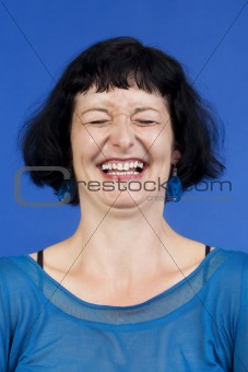 portrait of middle-aged woman with dark hair laughing - isolated on blue