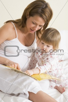 Pregnant woman in bedroom reading book with daughter
