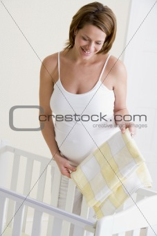 Pregnant woman setting up baby crib smiling