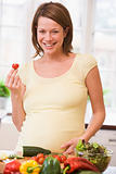 Pregnant woman in kitchen making a salad smiling