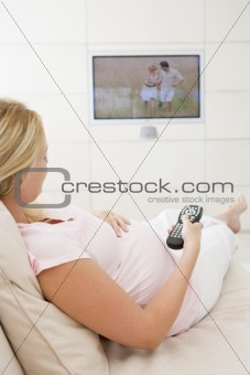 Pregnant woman watching television using remote control