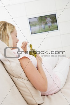 Pregnant woman watching television and eating pickles smiling