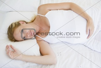 Pregnant woman lying in bed smiling