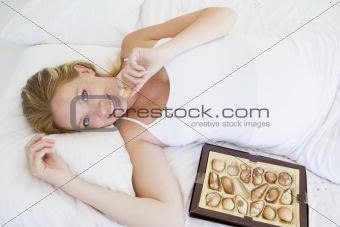 Pregnant woman lying in bed with chocolates smiling