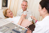 Pregnant woman getting ultrasound from doctor with husband looki