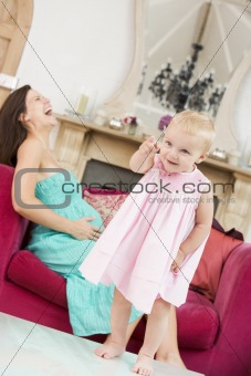 Pregnant mother holding belly in pain with daughter pointing in