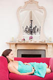 Pregnant woman lying in living room smiling