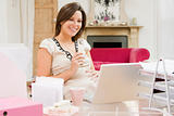 Pregnant woman in home office with laptop eating and smiling