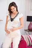 Pregnant woman standing in living room smiling