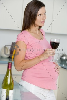 Pregnant woman in kitchen with glass of red wine