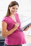Pregnant woman at work writing in binder smiling
