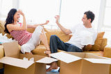 Couple playfully unpacking boxes in new home smiling
