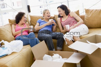 Three girl friends relaxing with coffee by boxes in new home smi