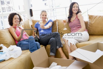 Three girl friends relaxing with champagne by boxes in new home