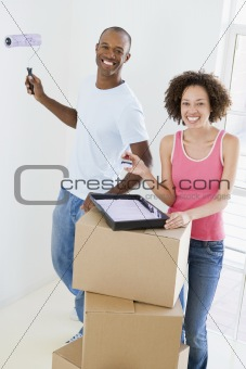 Couple with roller and paint in new home smiling