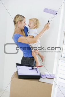 Mother holding son while painting room in new home smiling