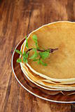 traditional American pancakes on a plate with a branch mint on a brown background