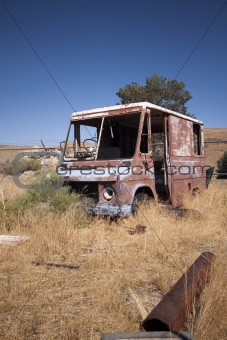 An old abandoned vintage delivery truck van in a field