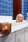Beautiful young woman in bathtub with eyes closed