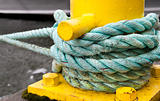 Twisted green rope around a yellow pier