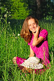 Beautiful woman sitting in grass and laughs