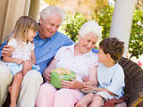 Grandparents with grandchildren on patio with gift smiling