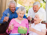 Two couples on patio with champagne and gift smiling