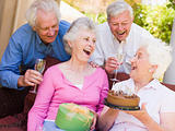 Two couples on patio with cake and gift smiling