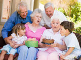 Grandparents and grandchildren on patio with cake and gift smili