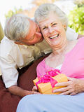 Husband giving wife gift on patio kissing her and smiling