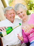 Couple on patio drinking champagne and smiling