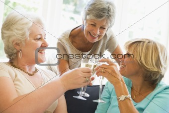 Three women in living room toasting champagne and smiling