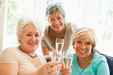 Three women in living room drinking champagne and smiling