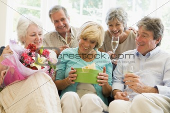 Five friends with champagne and gifts in living room smiling
