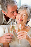 Couple in living room toasting champagne kissing and smiling