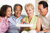 Two couples in living room with cake smiling
