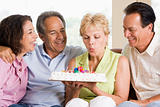Two couples in living room smiling with woman blowing out candle