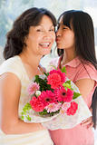 Granddaughter kissing grandmother on cheek holding flowers and s
