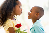 Young boy giving young girl rose and smiling