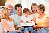 Family in living room smiling with young boy blowing out candles
