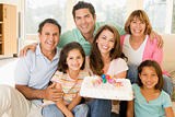 Family in living room with cake smiling