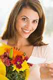 Woman holding flowers and note smiling