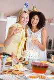 Two women at party holding drinks standing by food table smiling