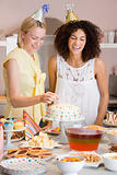 Two women at party putting candles in cake smiling
